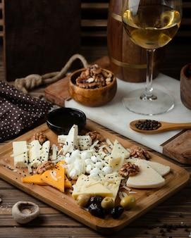 Plato de queso sobre tabla de madera con vino blanco