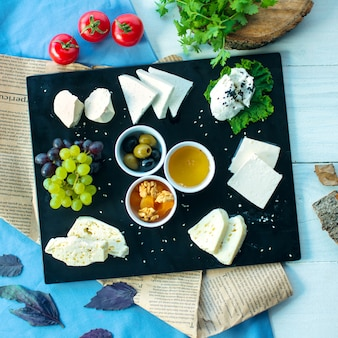 Plato de queso superior servido con uvas de miel y aceitunas en vinagre