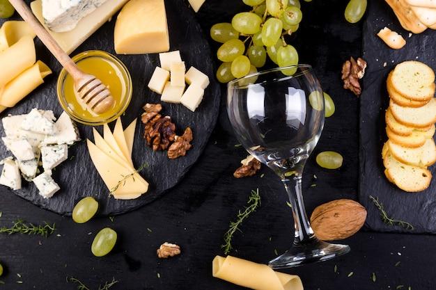 Plato de queso. surtido de queso con nueces, pan y miel en placa de pizarra de piedra.