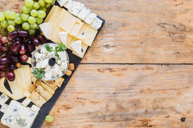 Plato de queso con uvas en tablero de pizarra negro sobre la mesa