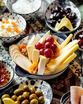 Plato de queso con uvas para vino en la parte superior