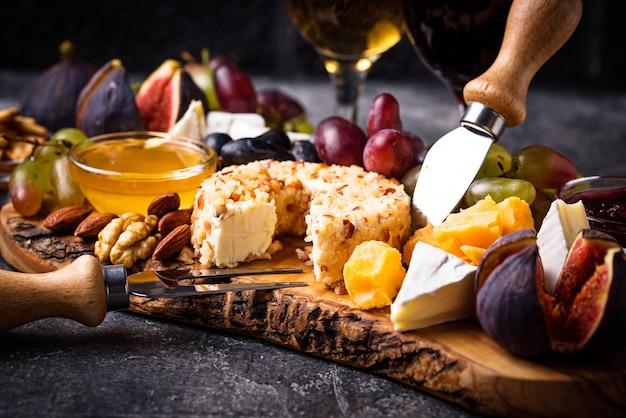 Plato de queso con uvas y vino.