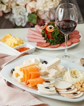 Plato de queso con vista lateral de vino tinto