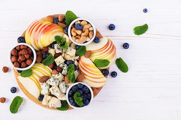 Plato de quesos con una variedad de quesos, arándanos, manzanas, nueces en mesa blanca. plato de queso italiano y fruta. vista superior, arriba