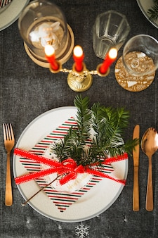 Plato con ramita y cinta junto a cubiertos y velas.