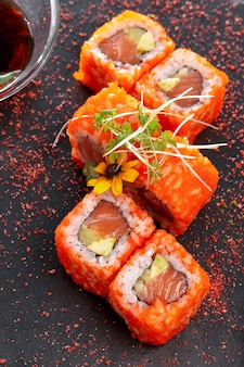 Plato rectangular negro con sushi, aislado en blanco