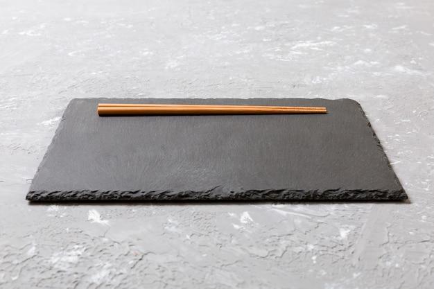 Plato rectangular de pizarra con palillos para sushi sobre mármol negro.