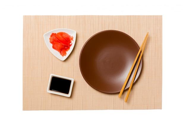 Plato redondo marrón vacío con palillos para sushi y salsa de soja, jengibre sobre estera de sushi marrón.
