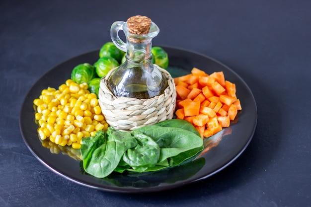 Plato con repollo, zanahorias, maíz y espinacas.