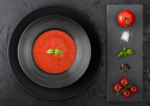 Plato de restaurante negro de cremosa sopa de tomate en mesa negra con tabla de cortar de piedra y tomates crudos, pimienta y sal. vista superior