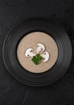 Plato de restaurante negro de cremoso castaño champiñón sopa de champiñones en negro. vista superior.