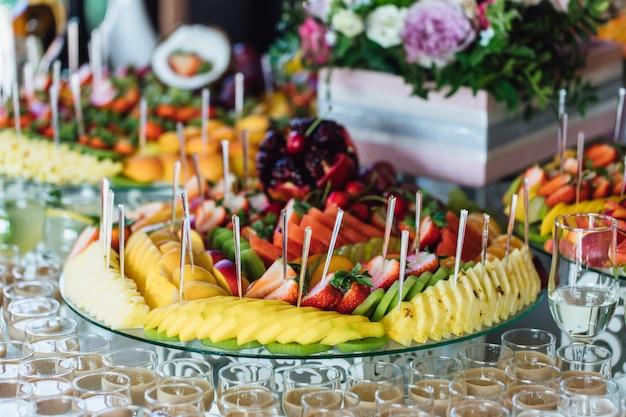 Plato con rodajas de frutas exóticas y vasos llenos de bebidas alcohólicas.