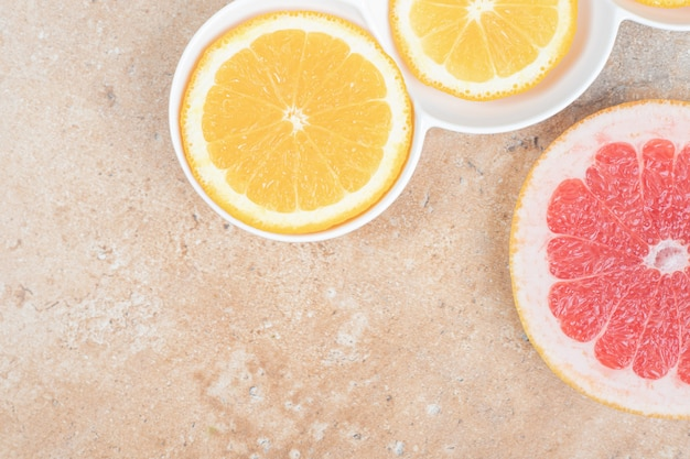 Plato de rodajas de limón y pomelo sobre fondo de mármol.