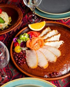 Plato de rodajas de pescado con salmón ahumado con guarnición de verduras