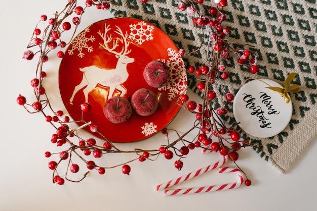 Plato rojo con una imagen de un ciervo, manzanas rojas, bastón de caramelo