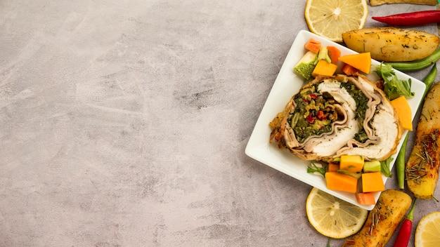 Plato con rollo de pollo y verduras en mesa de concreto