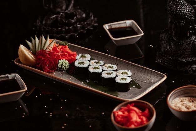 Plato de rollos de sushi con aperitivos.
