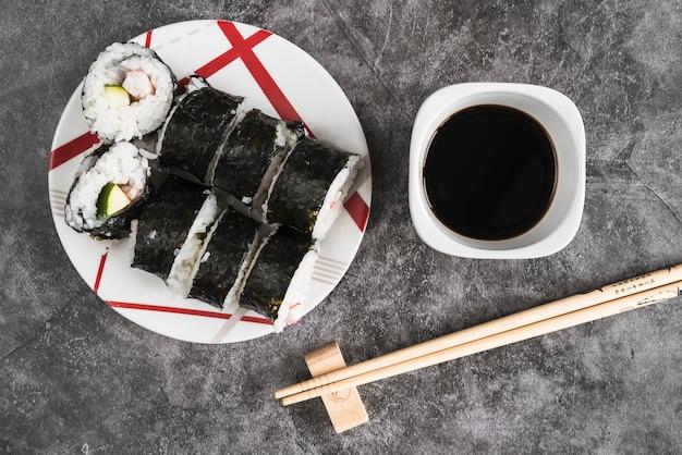 Plato con rollos de sushi junto a salsa de soja y palillos.