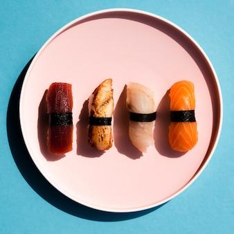 Plato rosa grande con sushi sobre un fondo azul.