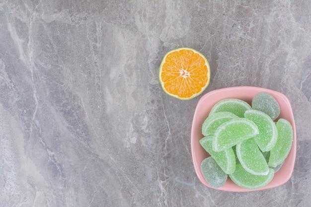 Un plato rosa de mermeladas y una rodaja de naranja sobre fondo de mármol.