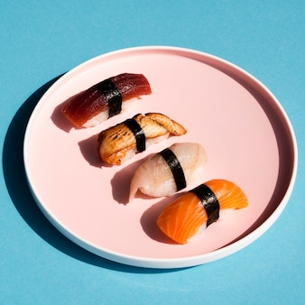 Plato rosa con sushi sobre fondo azul.