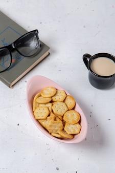 Plato rosa de vista distante superior con galletas y patatas fritas junto con gafas de sol y una taza de leche en el refrigerio de la foto de la galleta crujiente de fondo claro