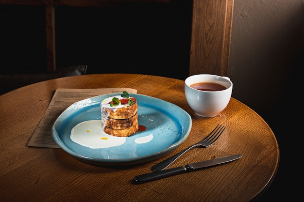 El plato con sabrosos panqueques en mesa de madera