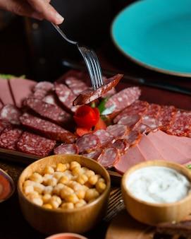 Plato de salami con rodajas de salchicha derivado con salados, salsa sobre tabla de madera