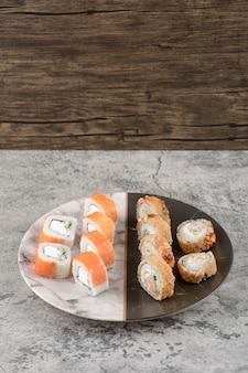 Plato de salmón y rollos de sushi calientes colocados sobre una mesa de mármol