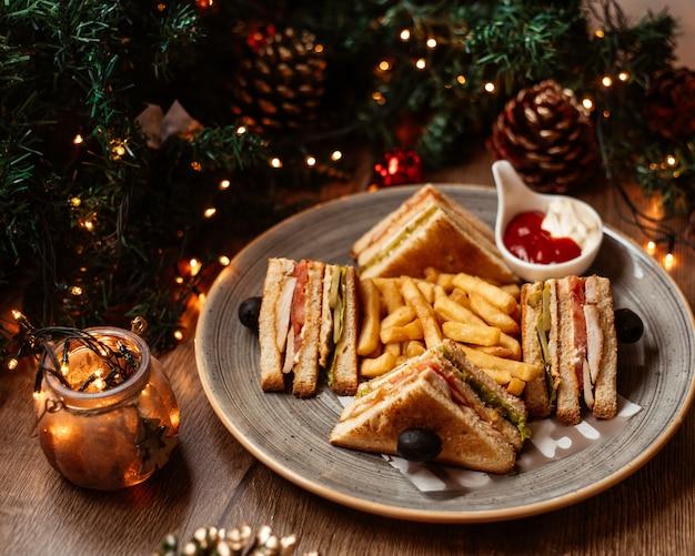 Un plato de sándwich club servido con papas fritas, mayonesa y salsa de tomate