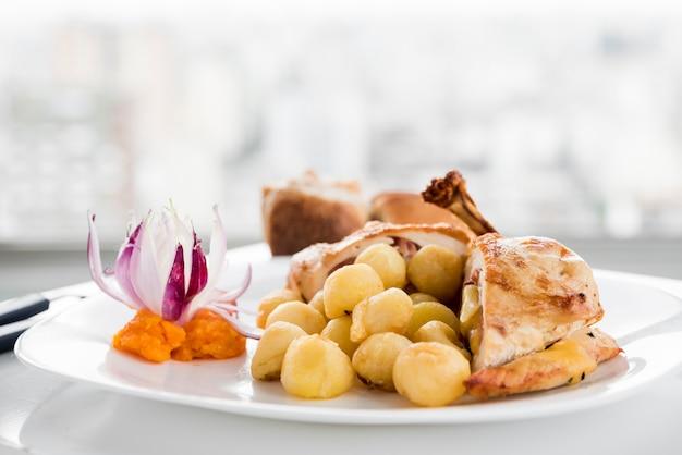 Plato servido con pechuga de pollo y ñoquis.