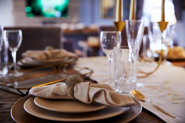 Plato sobre el que descansa una servilleta blanca, copas de cristal vacías sobre la mesa