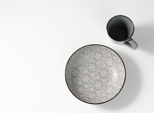 Plato de sopa de cerámica gris vacío y taza vacía en la mesa blanca, utensilios