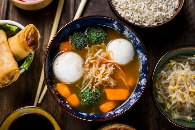 Plato de sopa de fideos clara con bola de pescado y vegetales en el escritorio de madera