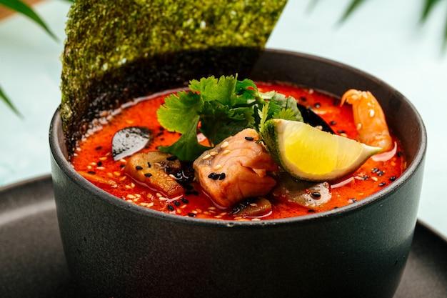 Un plato de sopa tom yam con mariscos, pescado rojo y nori