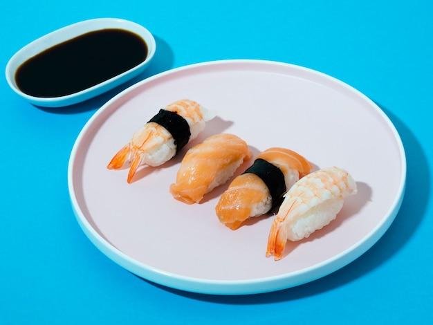 Plato de sushi blanco y tazón de salsa de soja sobre un fondo azul.