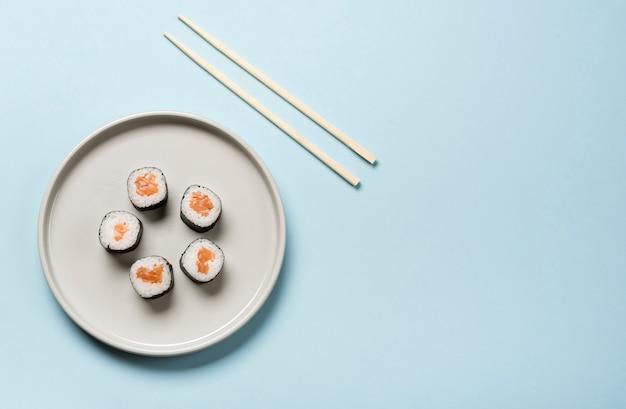 Plato de sushi japonés minimalista sobre fondo azul.