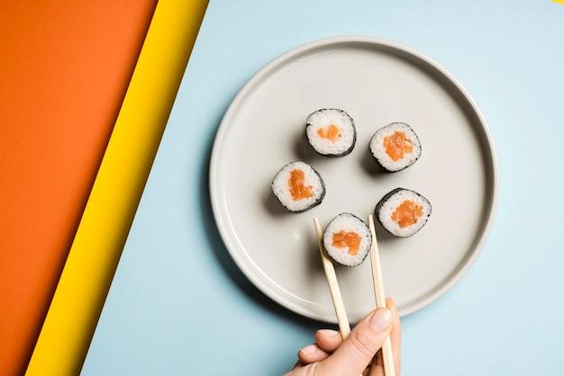 Plato de sushi japonés con palillos