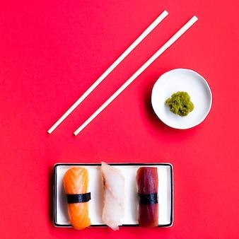 Plato de sushi con palitos de wasabi y chop sobre un fondo rojo.