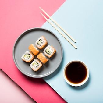 Plato de sushi plano con palillos y salsa de soja