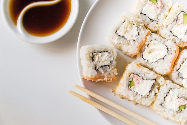 Plato de sushi con salsa y palillos