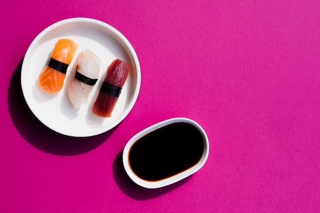 Plato de sushi con tarro de salsa de soja