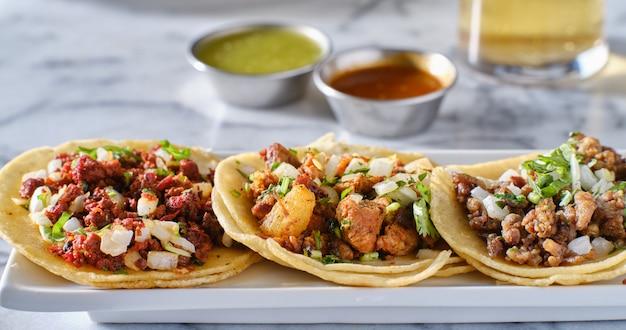 Plato de tacos callejeros mexicanos con carne asada, chorizo y al pastor en tortillas de maíz