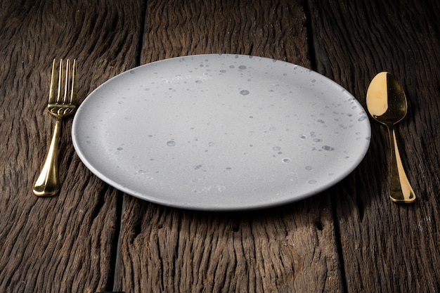 Plato tenedor cuchara sobre madera clara y sin profundidad de campo.