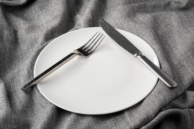 Plato tenedor cuchara sobre tela ropa clara y sin profundidad de campo
