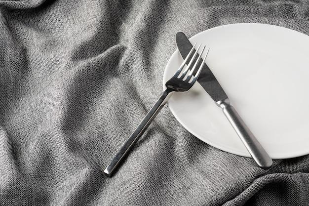 Plato tenedor cuchara sobre tela ropa fondo claro y sin profundidad de campo