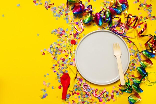 Plato con un tenedor y decoración de fiesta