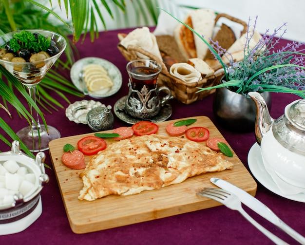 Plato de tortilla con salchichas y tomates, servido con té, aceitunas, pan y limón.