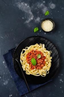 Plato tradicional italiano fettuccine pasta con salsa boloñesa, albahaca y queso parmesano en placa negra sobre superficie de madera oscura.