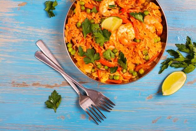 Plato tradicional de paella española con mariscos, guisantes, arroz y pollo